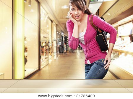 Cute lady looking at a shop window in shopping center