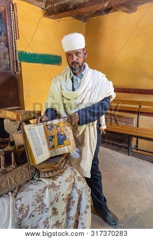 Yeha, Tigray Region, Ethiopia - April 28, 2019: An Orthodox Priest Shows A Painted Holy Bible From T