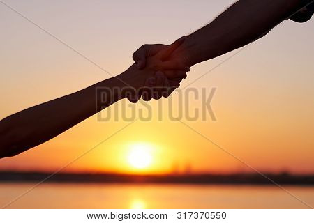 Giving A Helping Hand. Silhouette Two Hands, Man And Woman, Holding Tight At Sky Sunset