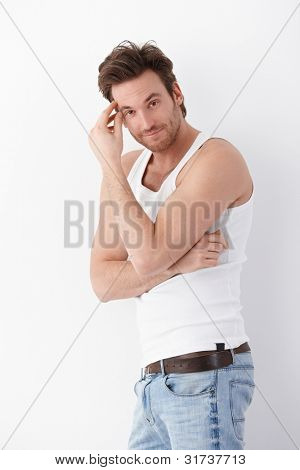 Sexy young man wearing undershirt and jeans, posing at white wall, smiling.