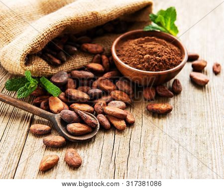 Raw Cacao Beans In Burlap Bag And Bowl With Cacao Powder  On A Wooden Table