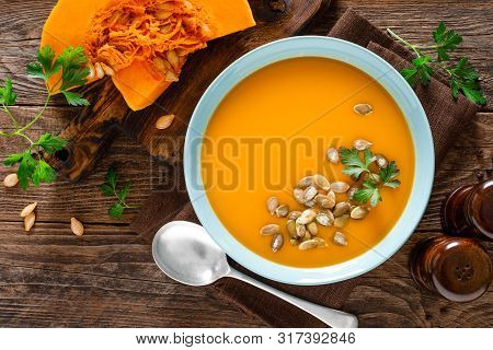 Pumpkin Soup. Vegetarian Soup With Pumpkin Seeds In Bowl On Wooden Table, Top View