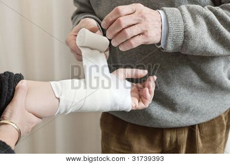 Doctor applying bandage on patient's wounded hand at the clinic