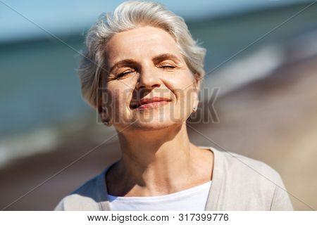 people and leisure concept - portrait of happy senior woman enjoying sun on beach