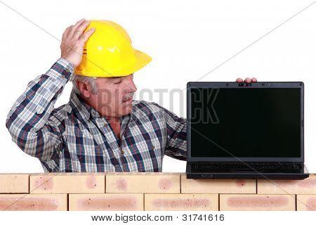 A mason with a laptop.