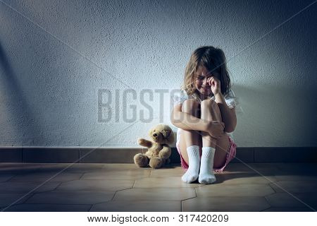 Sad Child Girl Crying Sitting On The Floor
