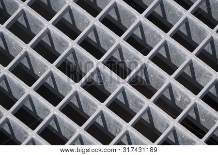 square geometry of the iron plates, sturdy bars. play of light and shadow, screensaver, background. diagonal lattice background from metal. Gray tint. poster