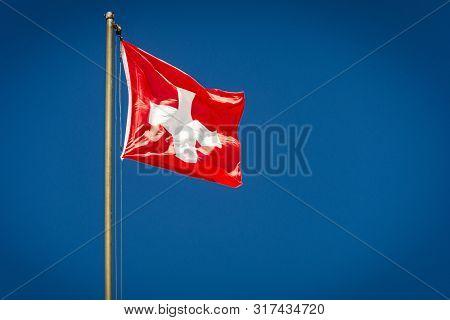 Swiss Flag Fluttering Against Clear Blue Sky