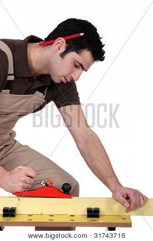Man sanding plank of wood