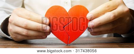 A Man Collects A Broken Heart In His Hands. Concept Of Love And Relationships. Family Psychotherapis
