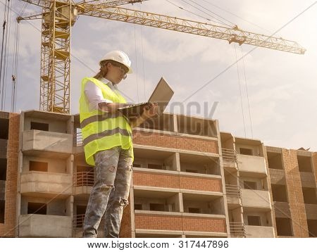 Portrait Of Female Builder Working On Laptop At Construction Site Of High Rise Building. Erection Of