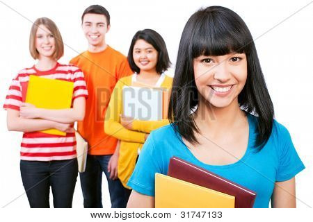 Happy young teenager students standing and smiling with books