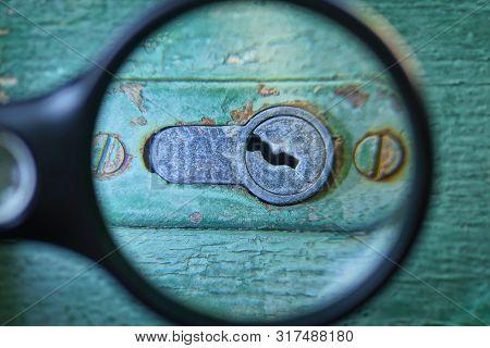 Black Magnifier Enlarges Old Gray Keyhole On Green Door Plank