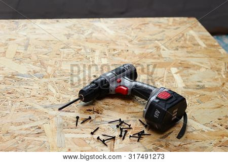 Screwdriver And Screws On Osb Plywood