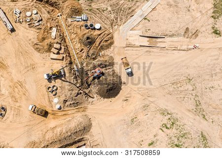 Truck Crane And Industrial Backhoe Installing Concrete Drains At Road Construction Site. Aerial View
