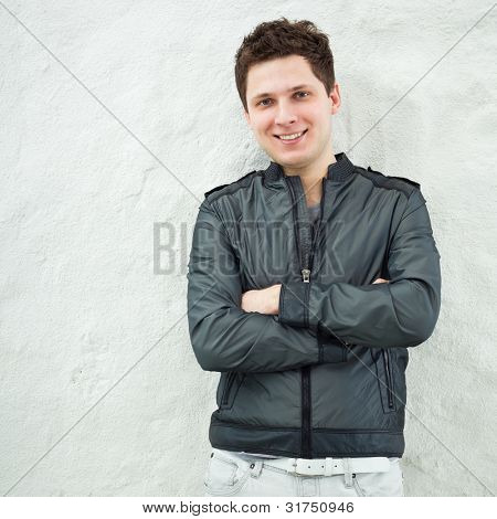 Young handsome man in casual clothes leaning against the wall