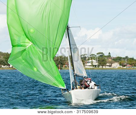 Kids Sailing Small Sailboat Head-on Closeup With A Fouled Green Spinnaker Sail. Teamwork By Junior S
