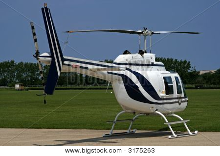 Side Of Grounded White Helicopter At Airport