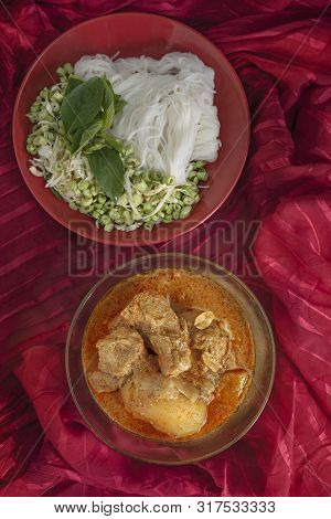 Massaman Pork Curry Served With Rice Noodles And Fresh Vegetables . Thai Style Coconut Milk Curry