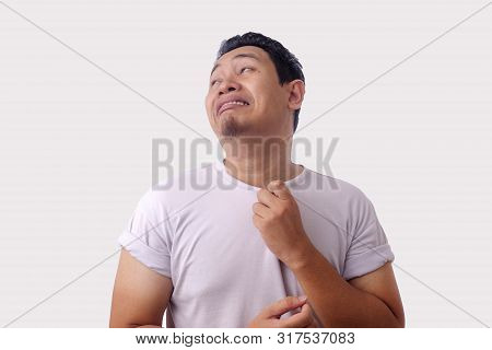 Funny young Asian man suffer from stifling hot, sweaty uncomfortable feeling poster