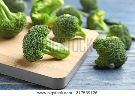 Board With Fresh Broccoli Florets On Blue Wooden Table, Closeup