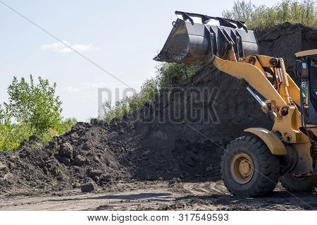 Wheeled Tractor With Bucket Clears The Soil Layer For Subsequent Construction