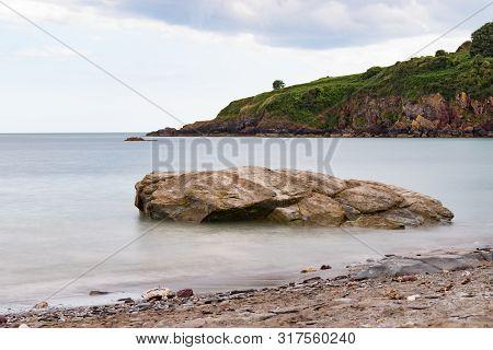 Smooth, Calm Sea Around A Shoreline Rock At St Marys Bay Beach In Torbay, Devon, With Some Coastline