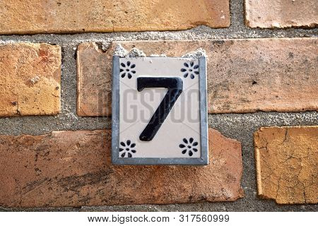 Sign With The Number 7 House Number Hanging On A Brick Wall