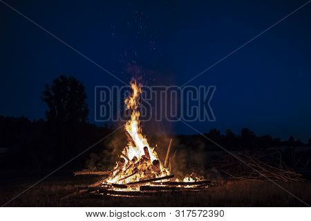 Campfire At Night, With Its Soothing Flickering Flames And Red And Orange Glow Of The Burning Logs A