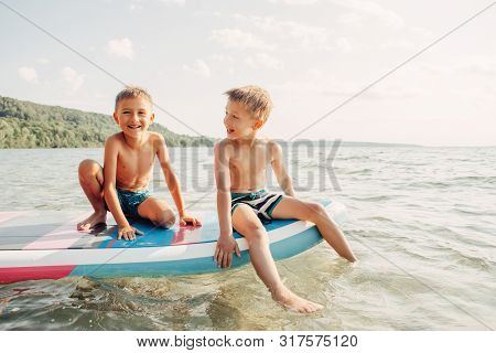 Two Smiling Caucasian Boys Kids Sitting On Paddle Sup Surfboard In Water. Children Friends Talking L