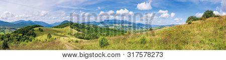 Wonderful Autumn Mountain Panorama. Pikui Peak Of Watershed Ridge Beneath Clouds. Trees On Grassy Ro