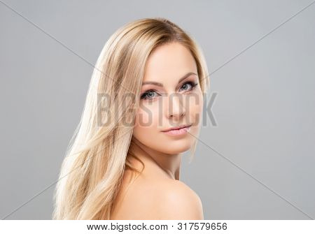 Studio portrait of young, beautiful and natural blond woman over grey background. Face lifting, plastic surgery, cosmetics and make-up concept.