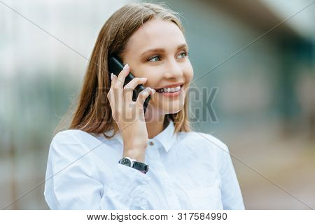 Young Famale Calling On A Smartphone. Attractive Businesswoman Talking By Phone. Office Building Bac