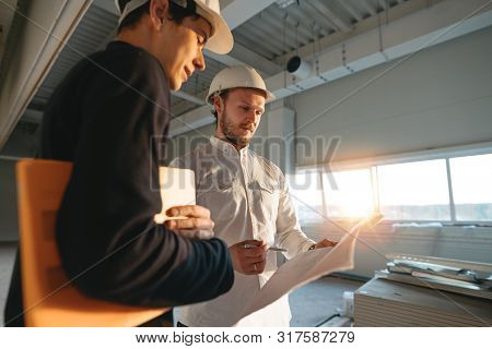 Building Industry. Young Engineer Discussing With Building Worker On Construction Site. Industrial E