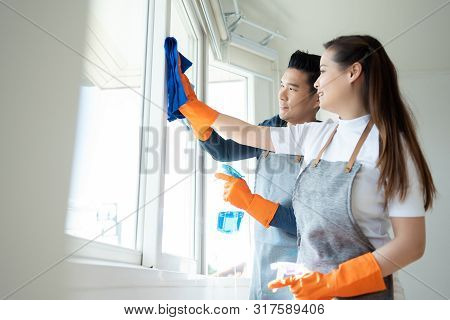 Young Asian Couple Cleaning House Together. Male And Female Wear Orange Rubber Gloves Are Wiping Dus