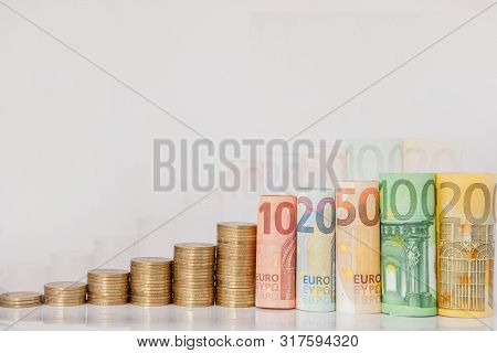 Ten, Twenty, Fifty, One Hundred, Two Hundred And Coins Euro Rolled Bills Banknotes On White Backgrou