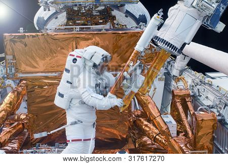 The Astronaut In A Space Suit, In An Outer Space, Is Engaged In Repair Of The Space Station. Element