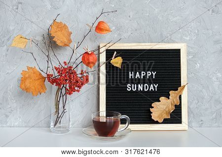 Happy Sunday Text On Black Letter Board And Bouquet Of Branches With Yellow Leaves On Clothespins In