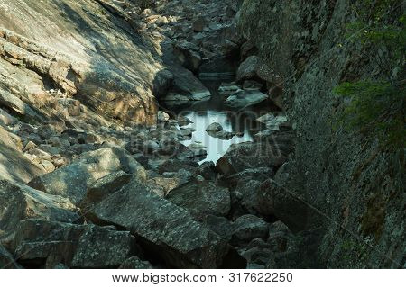 Rocky Dry River. Dry Watercourse Of The River With The Rocks And Water