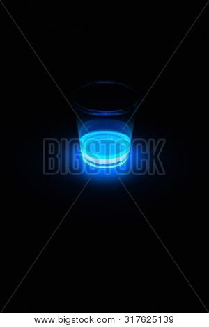 Blue glowing liquid used for glow sticks frequently used for entertainment at parties, concerts, and dance clubs. Glowing in a clear cup. Light emission by Chemiluminescence or chemoluminescence. poster