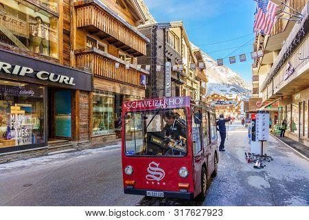 Zermatt, Switzerland - April 11, 2018: Unidentified Man Drives Electric Delivery Car By The Main Str