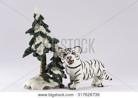 A Little White Begal Tiger With Blue Eyes Figurine Enjoys Walks Under A Show Covered Tree With White