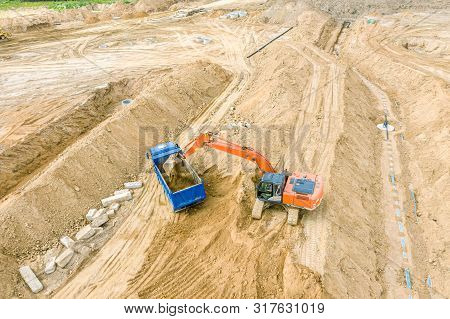 Industrial Excavator Loading Sand In Dump Truck At Construction Site, Top View
