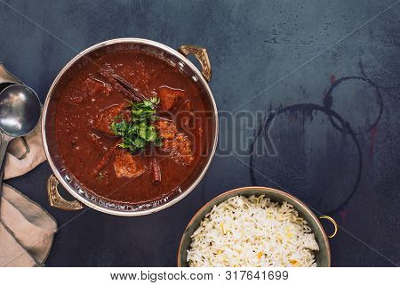 Kashmiri Lamb Rogan Josh. Slow Cooked Lamb Curry Served With Pulao Rice And Garnished With Coriander