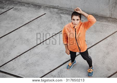 Upper View Motivated Confident Young Brunette Woman In Orange Running Jacket, Looking Up, Standing C