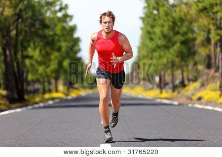 Running fitness sport man. Male runner sprinting on road - fit muscular male model training for marathon running fast on beautiful road in nature.