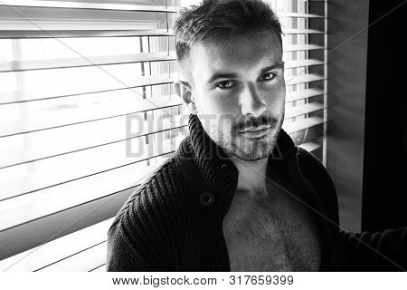 Portrait Of Attractive Man With Beard Standing Next To Window With Open Top Revealing Hairy Chest