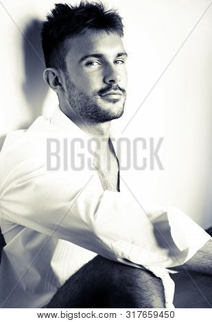 Portrait Of Handsome Man With Beard Wearing White Shirt Isolated Against Wall
