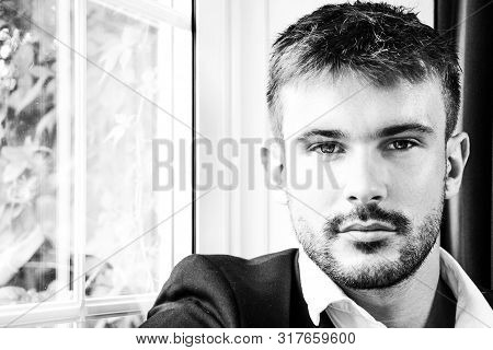 Attractive Man With Beard Wearing Shirt And Jacket Looking At Camera.