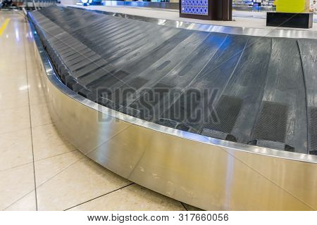 Suitcase On Luggage Conveyor Belt In The Baggage Claim At Airport